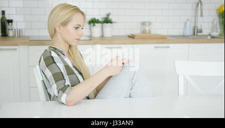 ... sur fond blanc · Belle jeune fille en chemise à carreaux et pantalon  home sitting on chair et en utilisant fb830b4d63c