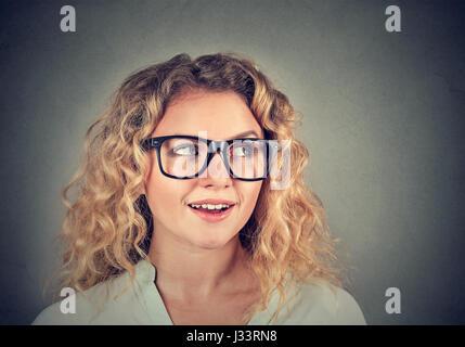 Wow. Closeup portrait of young woman surpris curieux isolé sur fond de mur gris. L'émotion positive expression visage Banque D'Images