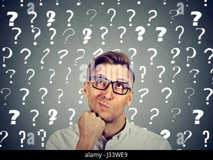 Bel homme confus réfléchie dans les verres a trop de questions et pas de réponse Banque D'Images