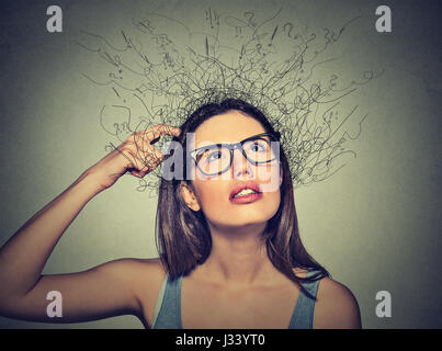 Closeup portrait jeune femme se gratter la tête, pensant à rêver avec la fonte du cerveau en lignes d'interrogation jusqu'à isolé sur fond gris