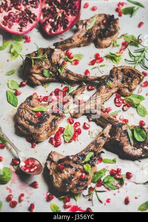 Côtes d'agneau grillées avec graines de grenade, menthe et romarin frais Banque D'Images