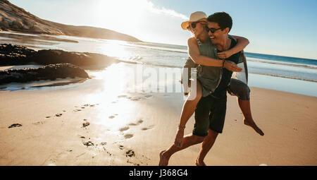 Man giving piggyback ride pour petite amie sur la plage. Happy young couple having fun on the Seashore, profitant Banque D'Images