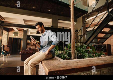 Vue latérale d'happy young man sitting in reading text message sur son téléphone portable et souriant. Creative Banque D'Images