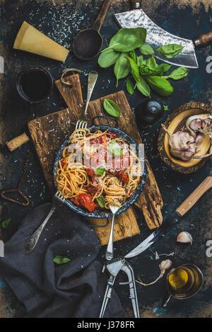 Spaghetti à la tomate et basilic et ingrédients pour faire des pâtes Banque D'Images