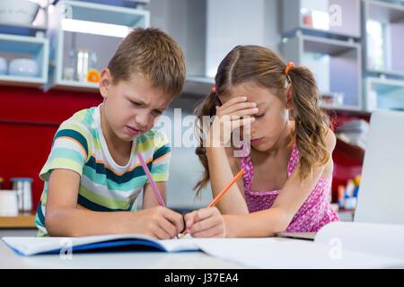 Frères et sœurs tendue à faire leurs devoirs dans la cuisine à la maison Banque D'Images