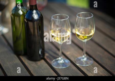Close up de vin blanc dans les verres en bouteilles sur table en bois Banque D'Images