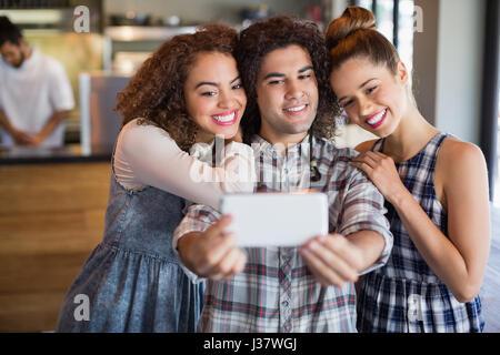 Jeune homme en tenant avec selfies female friends in cafe Banque D'Images
