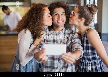 Portrait de jeune homme en tenant tout en selfies amis féminins embrassant in cafe Banque D'Images