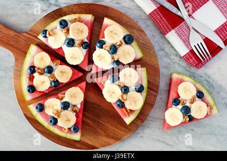 Tranches de pastèque pizza à la banane, les bleuets, les noix et le yogourt, vue ci-dessus sur le service à bord Banque D'Images