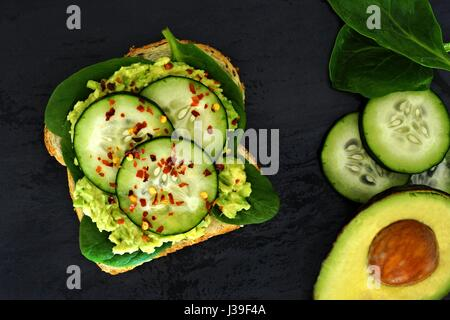 Sandwich à l'avocat ouvert avec le concombre et les épinards sur pain de grains entiers contre un arrière-plan en Banque D'Images