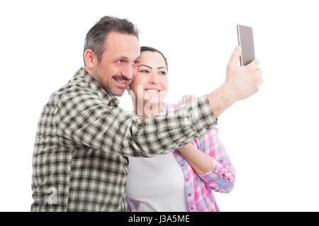 Jeune couple dans l'amour de prendre avec un téléphone mobile selfies et smiling isolated on white Banque D'Images