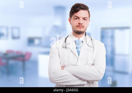 Portrait of attractive doctor holding les bras croisés et regardant la caméra avec zone publicitaire Banque D'Images