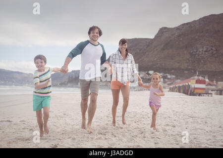 Portrait of family holding hands while running on sand at beach Banque D'Images