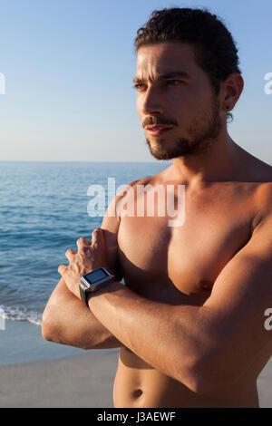 Homme musclé torse nu réfléchie with at beach Banque D'Images