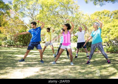 Groupe de personnes effectuant l'exercice d'étirement dans le parc par une journée ensoleillée Banque D'Images