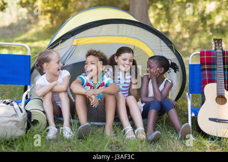 Happy friends sitting en tente de camping Banque D'Images