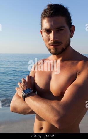 Portrait d'homme musclé torse nu debout avec les bras croisés at beach Banque D'Images