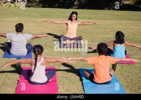 Happy young female trainer exercice s'étendant de l'enseignement aux enfants au parc Banque D'Images