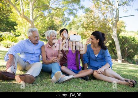 À l'aide de casque vr fille alors qu'il était assis avec sa famille dans le parc Banque D'Images