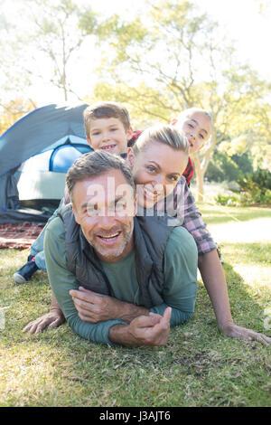 Smiling family stacking les uns sur les autres à l'extérieur de la tente Banque D'Images