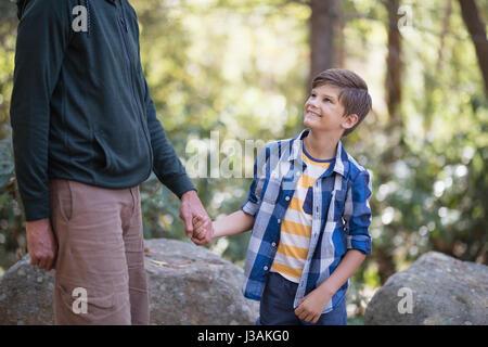 Section intermédiaire de père holding hand of smiling boy lors d'une randonnée en forêt Banque D'Images