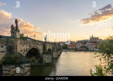 Recherche à travers le côté du pont Charles à Prague au coucher du soleil, avec le Château de Prague visible sur Banque D'Images