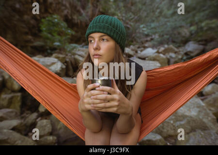 Young woman having coffee in forest