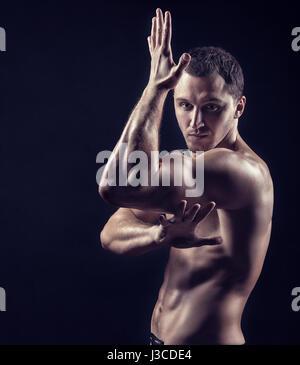 Beau jeune homme pratiquant les arts martiaux sur fond noir Banque D'Images