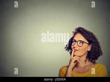 Portrait Portrait happy woman thinking looking up isolé sur fond de mur gris avec copie espace. Visage humain expressions, Banque D'Images