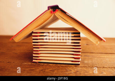 Arrière-plan de bâtonnets de bois sous la forme d'une maison sur table en bois brun avec le toit du livre Banque D'Images