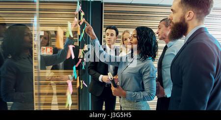 Groupe de gens d'affaires créatifs mettant brainstorming notes adhésives sur verre wall in office Banque D'Images