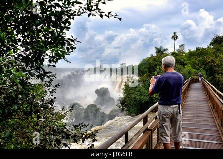 Man'prise d'une photo d'un d'Iguazu (aka Iguassu Falls ou Cataratas del Iguazu), province de Misiones, Argentine Banque D'Images
