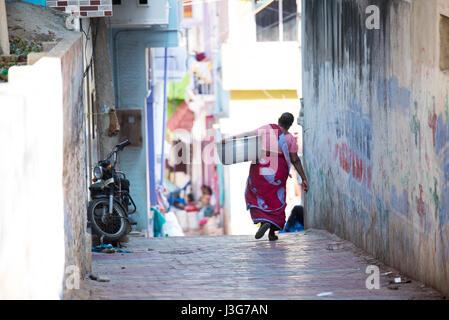 Femme en costume traditionnel portant un grand bol par une étroite ruelle de Kanyakumari, India Banque D'Images