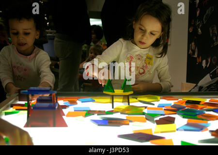 Les petites filles avec des formes colorées sur table lumineuse Banque D'Images
