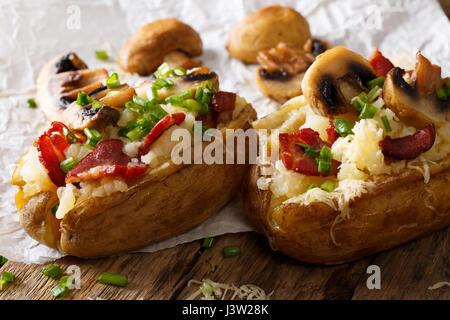 Des pommes de terre au four avec du bacon, champignons, oignons et fromage sur la table horizontale. Banque D'Images
