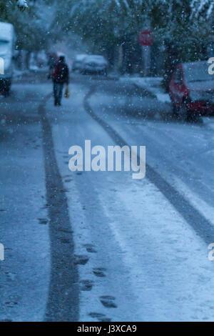 Homme marchant entre des traces de roues de voiture dans une tempête de neige en avril. Effet du réchauffement climatique. Banque D'Images