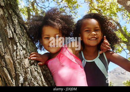 Portrait de deux jeunes sœurs, climbing tree Banque D'Images
