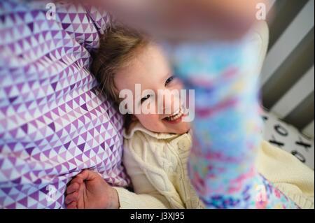 Girl laughing en jouant sur lit de jour Banque D'Images