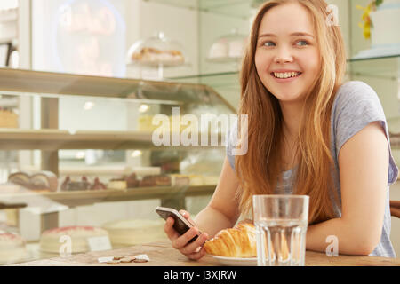 Girl in cafe smiling holding smartphone Banque D'Images