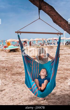 Fille poussant frère en hamac sur la plage de Poetto, Cagliari, Italie Banque D'Images