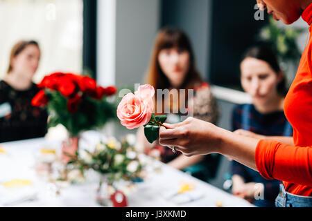 Un fleuriste à des étudiants en montrant rose atelier floral Banque D'Images