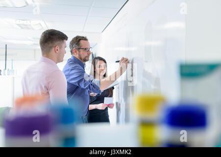 Les pharmaciens à l'aide de tableau blanc en réunion à l'usine pharmaceutique Banque D'Images