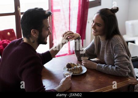 Couple sitting at table tenant les mains, boire du café Banque D'Images