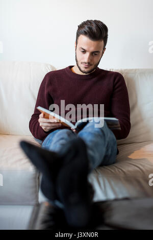 Young man relaxing on sofa, reading book Banque D'Images
