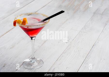 Cocktail cosmopolite sur blanc vintage table en bois. Avec l'espace pour votre texte