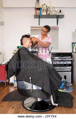 Coiffure féminine à l'aide de tondeuses sur boy's hairstyle dans barber shop Banque D'Images