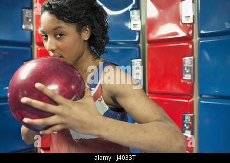 Une jeune femme tenant une boule de bowling. Banque D'Images