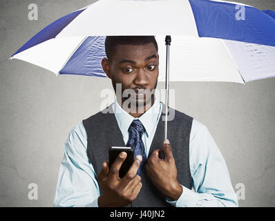 Closeup portrait sceptique confondu corporate business man reading breaking news on smart phone holding umbrella Banque D'Images