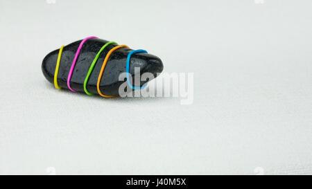 Être différent l'une pierre noire avec des bandes de couleur sur fond lumineux