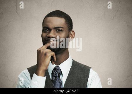 Closeup portrait jeune homme d'affaires perplexes penser profondément à décider quelque chose de doigt sur les lèvres à fond noir isolé confus. Emotio